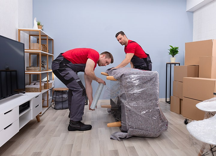 movers are wrapping a couch